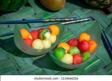 two cups filled with fruit balls of all colors, melon, watermelon, kiwi
