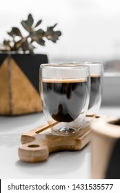 Two cups of fresh espresso on a wooden tray, on a white background. Sunlight from the window and plant in the planters.