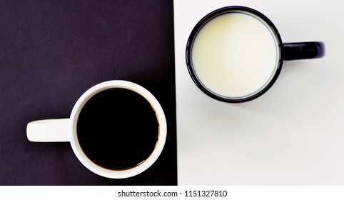 Two cups in front of a half black and half white background, one cup contains coffee, the other milk and both creat a contrast, concept for yin and yang with coffee cups