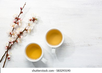 Two cups of green tea and  branches of blossoming apricot  on  old wooden shabby background