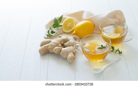 Two cups of healthy ginger tea with mint leaves and lemon on white table. Space for your text