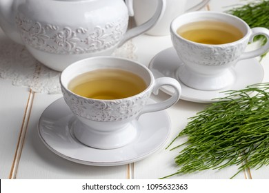 Two cups of horsetail tea with fresh Equisetum arvense plant on a white wooden table
