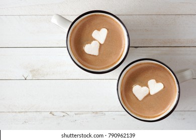Two cups of hot chocolate with heart shaped marshmallows over a white wood background