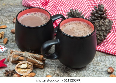 Two cups of hot chocolate and spices close-up on a background of red checkered fabric. Christmas holidays