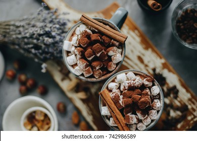 Two cups of hot cocoa with marshmallows and cinnamon, view from above