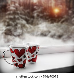 two cups with hot coffee or tea along with hearts on the background of the winter forest. decorations for Valentine's Day or wedding