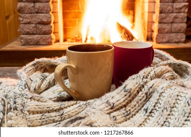 Two cups for hot tea or coffee and cozy warm scarf near fireplace, in country house, winter vacation, horizontal.