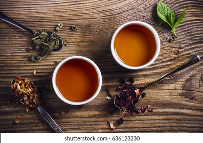 Two cups of loose leaf tea on a wooden table, top view