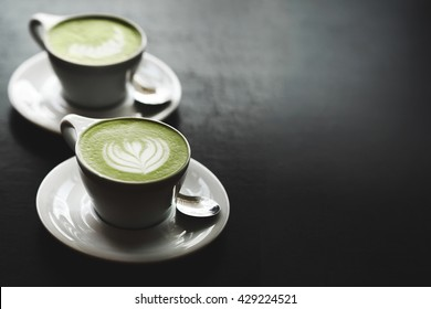 Two cups of matcha latte with latte art on black table. Top view. Place for text