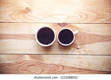 Two cups of morning coffee on wooden table. View from above