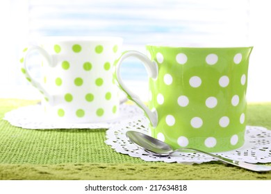 Two cups on napkin on table on light background