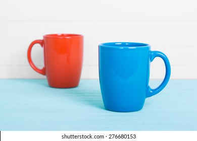 two cups in perspective view, on wood planks as background
