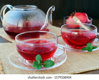 Two cups of pomegranate tea and tea pot with mint leaves over burlap on dark background