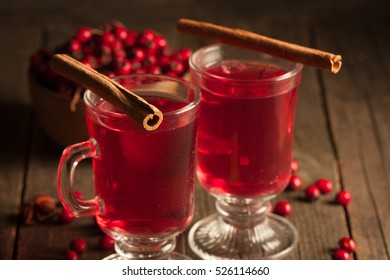 Two cups of red hot tea drink with fruits and spices on a wooden background. Mulled wine with cinnamon, anise and red berries. Winter hot drinks concept.