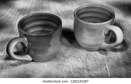 """Two cups shot in black and white on a wood background. Used """"painting by light"""" for this exposure."""