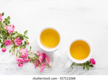 Two cups  of tea and branch of small pink roses on rustic table.