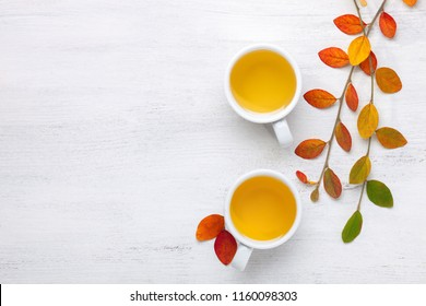 Two cups  of tea and colorful autumn leaves  on white rustic table.