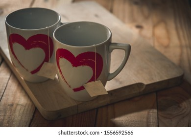 two cups of tea with a heart designed in a quiet and rustic atmosphere