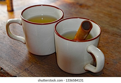 Two cups of tea made by dipping hollow bamboo canes filled with tea leaves into the hot water and letting it infuse.