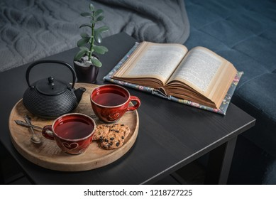 Two cups of tea on a serving tray on coffee table. Breakfast over sofa in morning sunlight. Cozy autumn or winter concept.