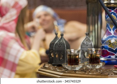 Two cups of tea on table in the foreground while people smoking water pipe in background