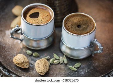 Two cups of Turkish coffee in authentic coffee ware, almonds in shell and cardamom pods over silver tray. Selective focus, shallow DoF