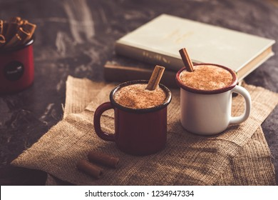 Two cups of Turkish salep (milky traditional hot drink) with cinnamon sticks on sack fabric