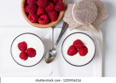 Two cups of yogurt with fresh raspberries and raspberry jam.Top down view