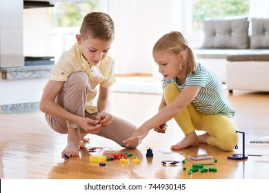 Two curious happy children playing with electric system game