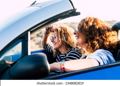 Two curly beautiful women friends drive and travel together on a convertible blue car having fun - outdoor happy leisure activity for cheerful people under the sun of summer - focus on second girl