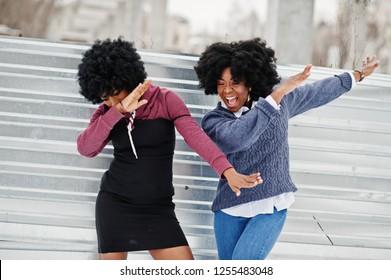 Two curly hair african american woman wear on sweaters posed at winter day, doing dab.