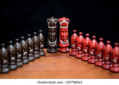 Two custom designed kings from a chess set on a wood surface.  They are lined up with the pawns flanking into the camera.