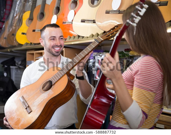 two customers choosing acoustic guitar in music instruments store