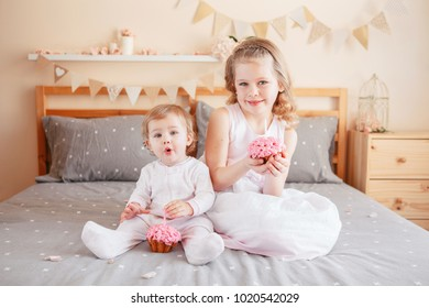 Two cute adorable white Caucasian girsl holding pink cupcakes celebrating birthday. Smiling children sitting together on bed in bedroom having fun. Home indoors cake smash first year concept