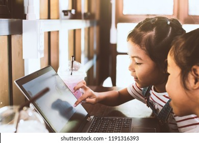 Two cute asian child girls using and playing on laptop in the cafe together with fun and happiness