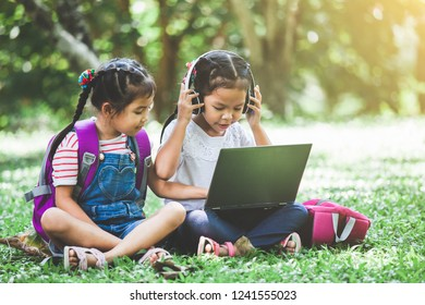 Two cute asian child girls using laptop in the park together with fun and happiness. Back to school concept