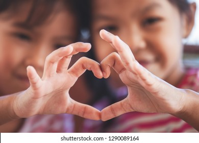 Two cute asian child girls making heart shape with hands together with love