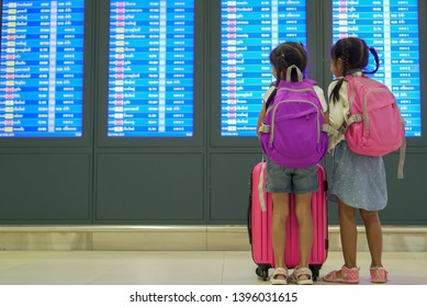 Two cute asian child girls with backpack checking their flight at information board in international airport terminal