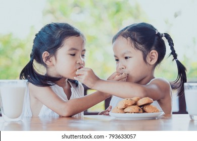 Two cute asian little child girls are eating cookies with milk for breakfast together with happiness