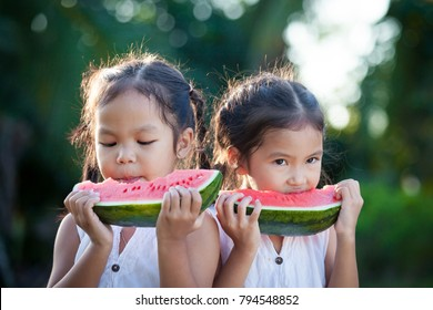 Two cute asian little child girls eating watermelon fresh fruit in the garden together