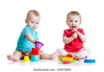Two cute babies playing with cup toys. Children toddlers girl and boy sitting on floor, isolated on white background.