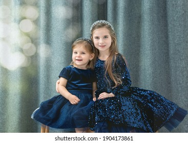 two cute baby girls sisters with blue eyes wear dark blue dresses sit on a decorative bench and hug