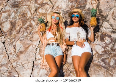 Two cute beautiful girls in Boho style dressed shirts shorts light cape bracelets necklaces, in the hair decorative feathers colored, straw hats, with pineapple in their hands on the background cliffs