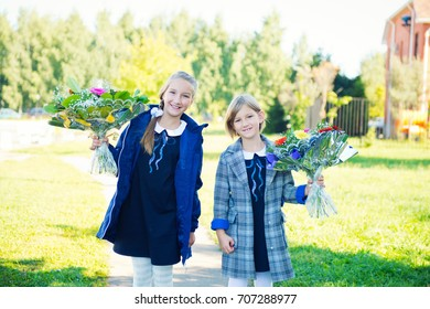 Two cute blond girls with flowers going to school at first day of autumn September