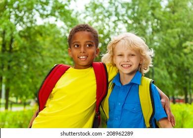 Two cute boys after school in a hug outside