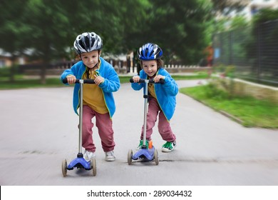 Two cute boys, compete in riding scooters, outdoor in the park, summertime
