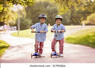 Two cute boys, compete in riding scooters, outdoor in the park, summertime on sunset