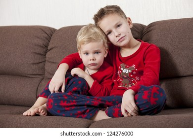 Two cute boys in pajamas sitting on the sofa embracing and looking in the camera
