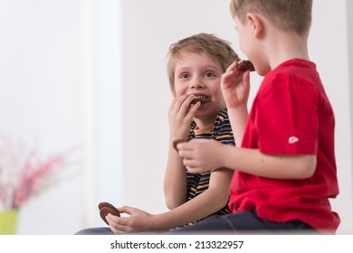 two cute boys sitting on couch. two friends eating cookies and talking