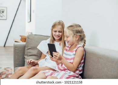 Two cute Caucasian blonde smiling girls sisters using cell phone.